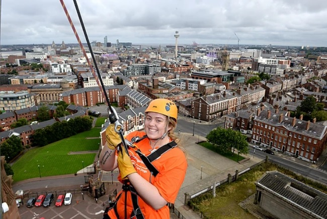 Smiling girl abseiling from cathedral
